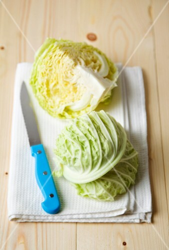 Savoy cabbage quarters on a tea towel with a knife