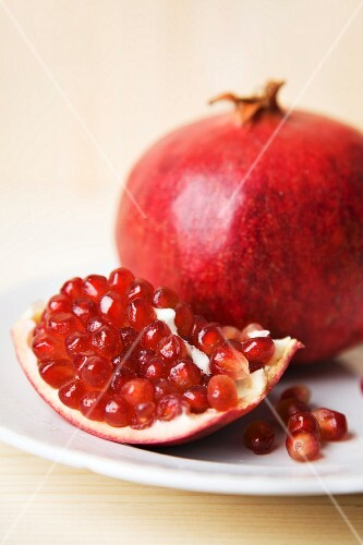 A piece of pomegranate and a whole pomegranate