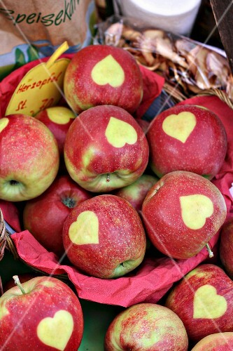 Red apples stencilled with hearts at a market