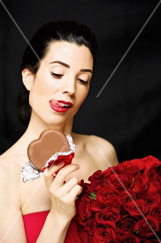 A dark haired woman holding a bunch of red roses and chocolate heart