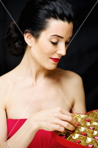 A dark haired woman wearing a red cocktail dress holding a box of pralines