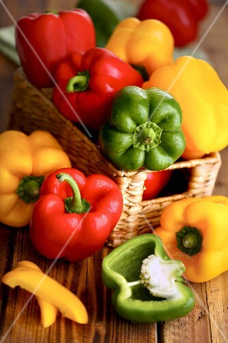 Peppers (yellow, green and red) in a basket and next to it