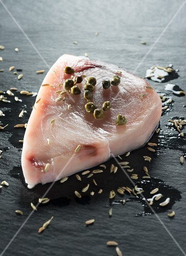 Swordfish with capers and fennel on a slate surface