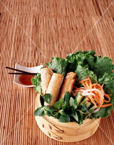 Vegetarian spring rolls on a bed of lettuce with daikon radish and carrots served with sweet chilli sauce