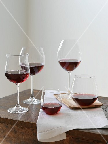 Various types of red wine glasses on a wooden table