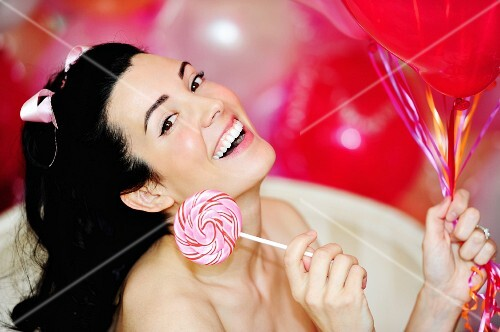 A dark haired woman holding a lolly and a bunch of balloons