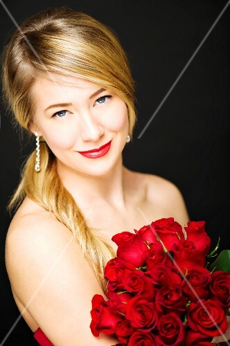 A young blonde woman wearing a cocktail dress and holding a bunch of red roses