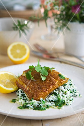 Fried cod fillets with a spicy coating on a bed of coriander rice