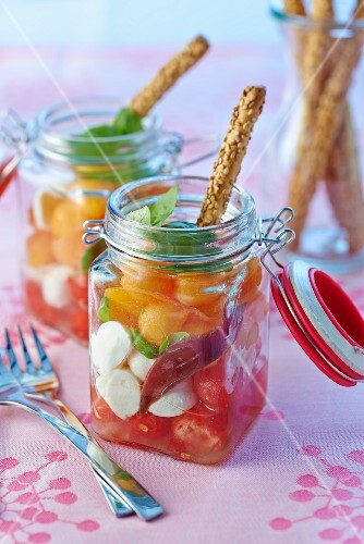 Melon and tomato salad with mozzarella and sesame seed sticks in preserving jars