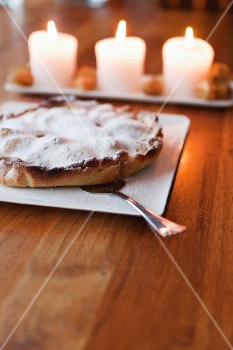 Pie dusted with icing sugar in front of lit candles