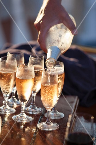 Champagne being poured into six glasses