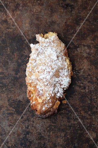 An almond croissant with icing sugar on a baking tray