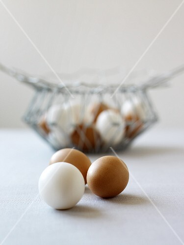 Brown and white egg in front of a wire basket
