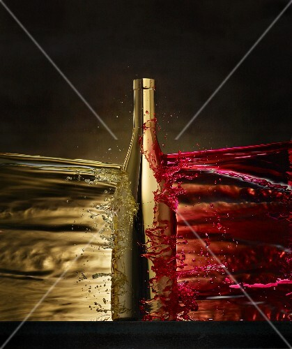 A golden wine bottle in between a splash of white and red wine