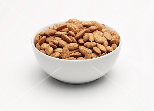 Unpeeled almonds in a white bowl