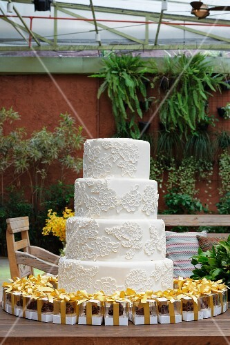 A white, four tier wedding cake with mini boxes of pralines as gifts