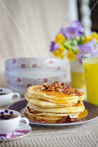 A stack of buttermilk pancakes with pecan nuts and maple syrup