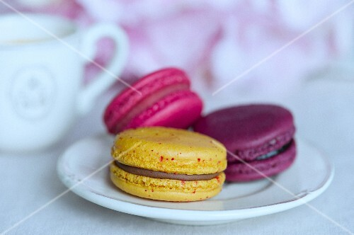 Three colourful macaroons on a white saucer