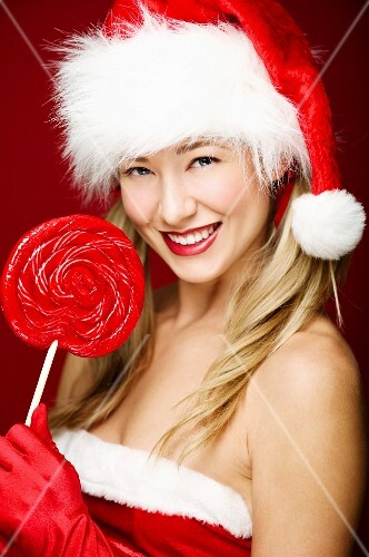 A young woman wearing a Father Christmas hat and holding a giant lolly
