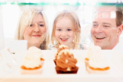 Parents and a child looking into a display cabinet filled with creamy cupcakes