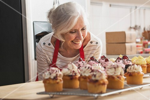 A happy grandmother looking at home-made cupcakes