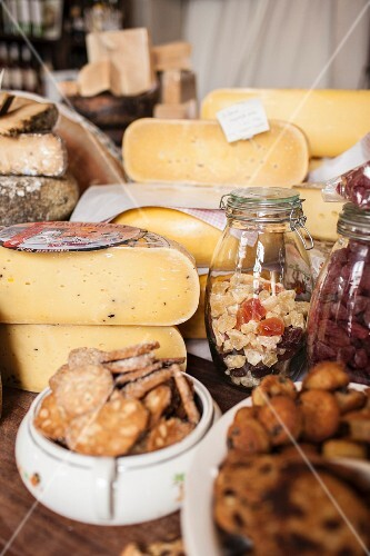 Various types of cheese, crackers and candied fruit in a delicatessen
