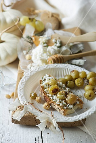 Crostino topped with goat's cheese, thyme, honey and grapes