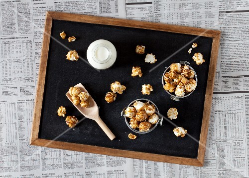 Small buckets of caramel popcorn and milk on a blackboard