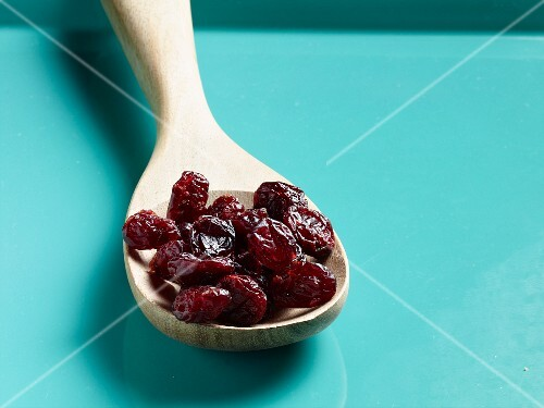 Dried cranberries on a wooden spoon