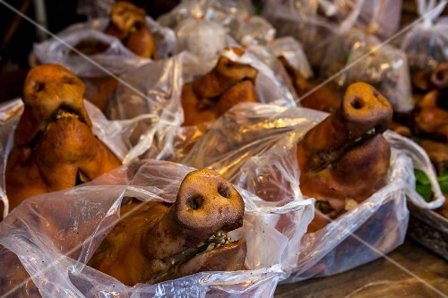 Cooked pig's heads in plastic bags on a market stand