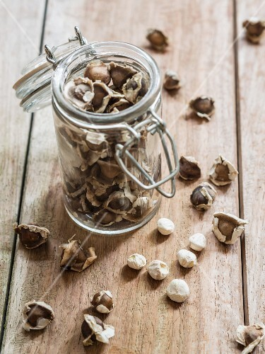 Moringa seeds in a jar on a wooden surface