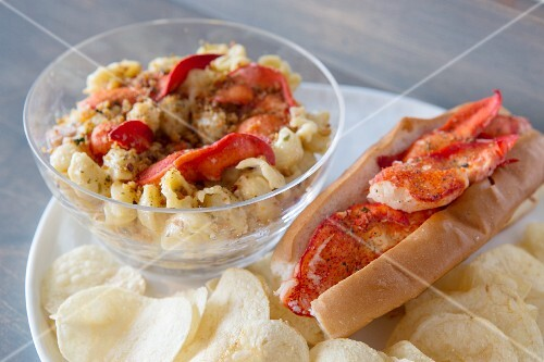 Grilled lobster on macaroni and cheese, a lobster roll and potato crisps