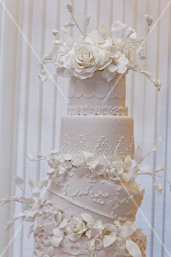 An artistically decorated wedding cake with elaborate flower decorations
