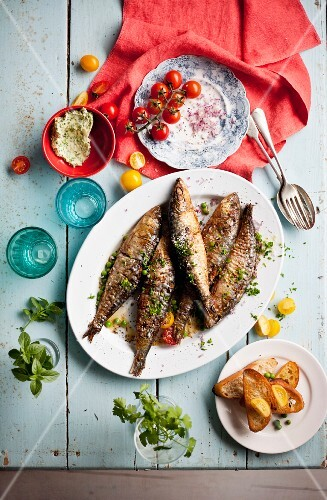 Fried sardines with herb butter, grilled bread and tomatoes