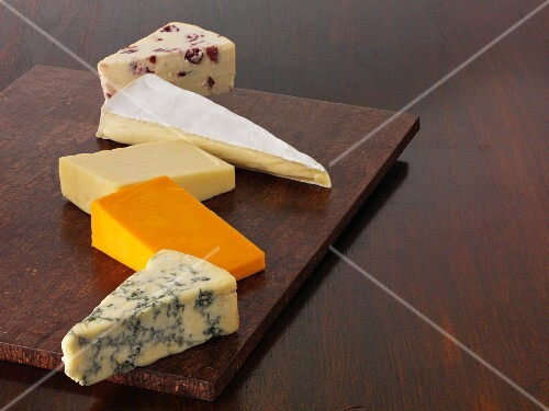 Various wedges of cheese on a wooden board