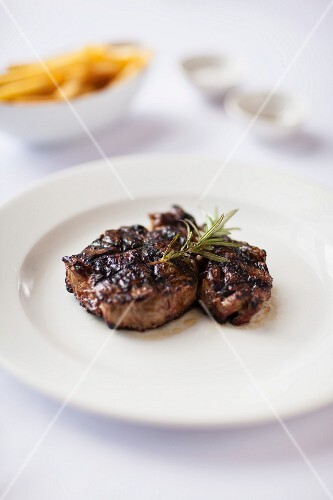 Grilled ribeye steak with sprigs of rosemary
