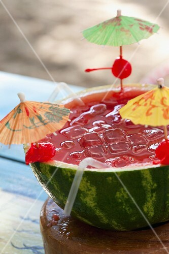 A tropical drink served in a halved watermelon with ice cubes and cocktail umbrellas