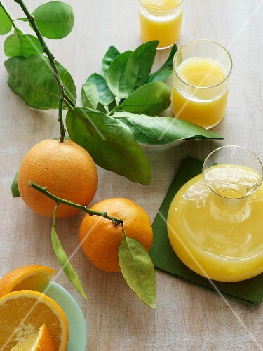 Oranges on a branch with orange juice in a carafe and glasses