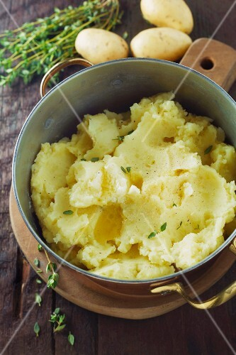 Mashed potatoes with thyme in a copper pot on a wooden surface