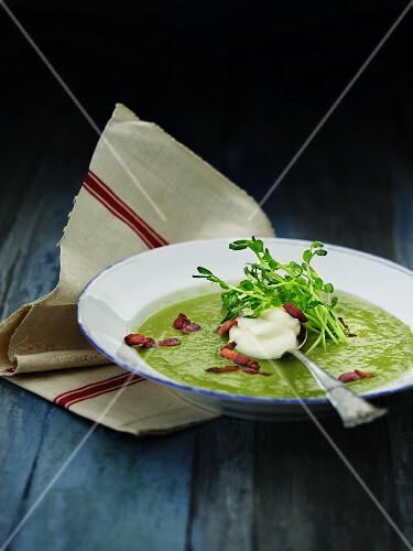 Cream of pea soup with bacon, crème fraîche and pea sprouts