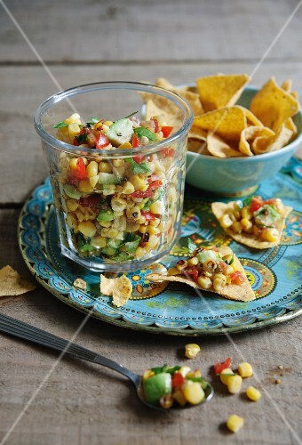 Sweetcorn and avocado salsa with limes and tomatoes served with tortilla chips