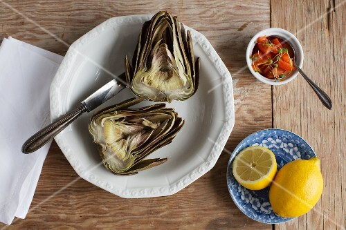 A boiled artichoke with tomato salsa and lemon