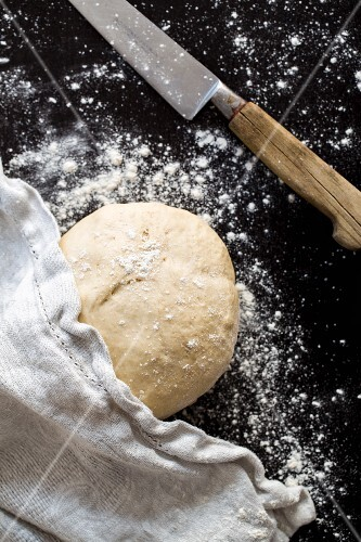 A ball of pizza dough with flour, a cloth and a knife