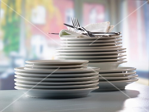 A stack of plates and fabric napkins with cutlery in front of a kitchen window