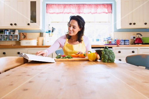 A woman sitting at a kitchen table with a cookbook preparing vegetables