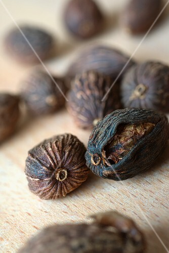 Dried black cardamom on a wooden surface