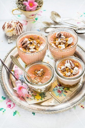 Mini cheesecakes in glass bowls with strawberries and meringues