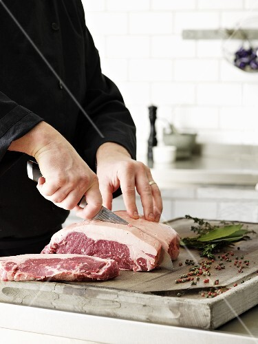 A chef cutting beef steak into portions