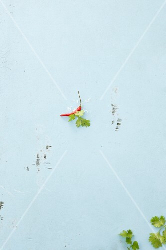 A chilli pepper and coriander leaves on a white surface