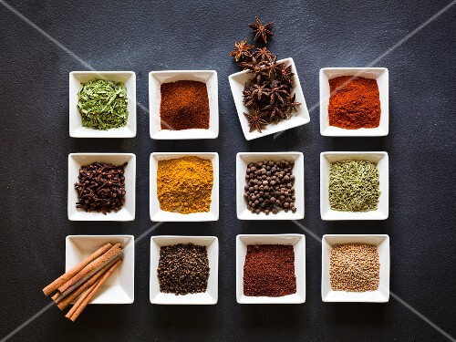 Various spices in square dishes on a chalkboard surface